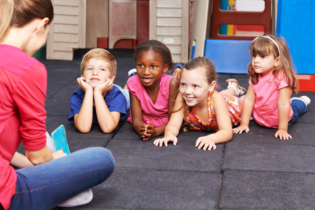 Nursery teacher reading story book to group of kids in kindergarten