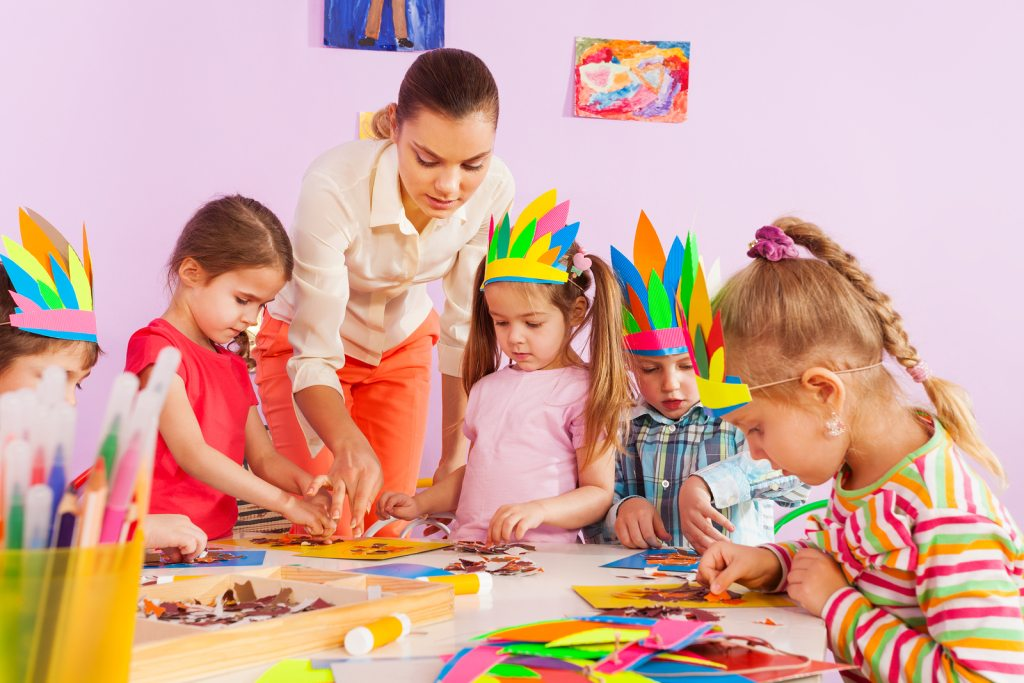 Teacher teaching preschool kids in art class