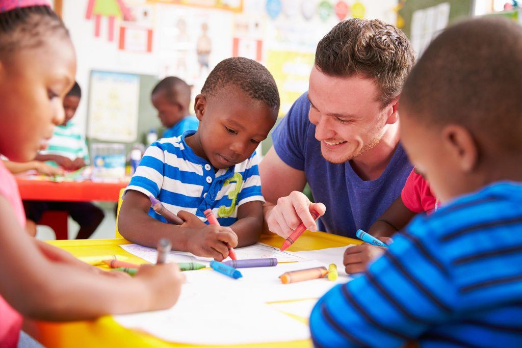 Male early childhood education teacher helping class