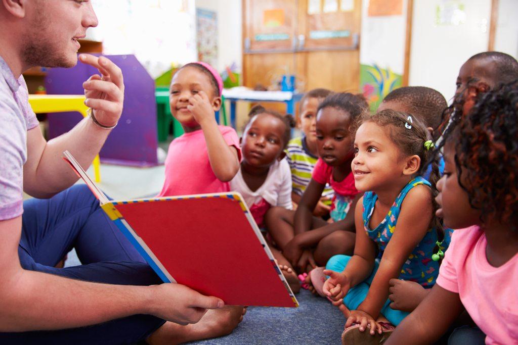 Volunteer teacher reading to a class of preschool kids