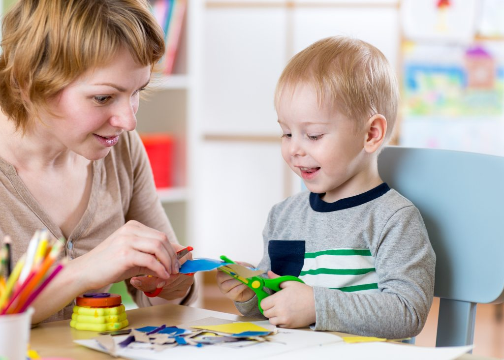 Woman teaches child handcraft at kindergarten or playschool